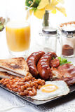 Full English breakfast with bacon, sausage, egg, baked beans and orange juice Stock Image