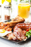 Full English breakfast with bacon, sausage, egg, baked beans and orange juice Stock Photos