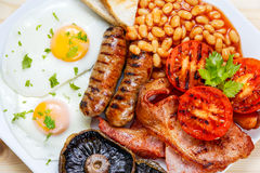 Full English breakfast with bacon, sausage, egg, beans and mushrooms Royalty Free Stock Photo