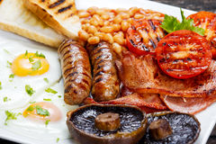 Full English breakfast with bacon, sausage, egg, beans and mushrooms Stock Image