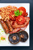 Full English breakfast with bacon, sausage, egg, beans and mushrooms Stock Images
