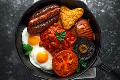 Full English breakfast with bacon, sausage, fried egg, baked beans, hash browns and mushrooms in rustic skillet, pan. Full English breakfast with bacon, sausage Royalty Free Stock Images