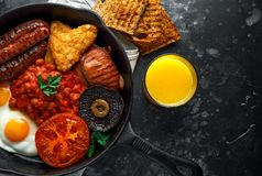 Full English breakfast with bacon, sausage, fried egg, baked beans, hash browns and mushrooms in rustic skillet, pan. Orange juice stock photo