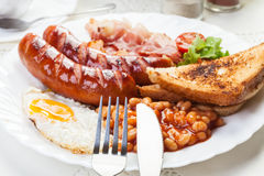 Full English breakfast with bacon, sausage, fried egg and baked Royalty Free Stock Images