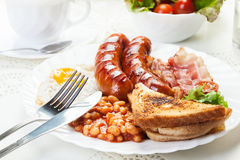 Full English breakfast with bacon, sausage, fried egg and baked Royalty Free Stock Photos
