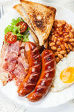 Full English breakfast with bacon, sausage, fried egg and baked beans Royalty Free Stock Photos