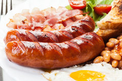 Full English breakfast with bacon, sausage, fried egg and baked beans Royalty Free Stock Photo
