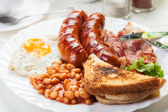 Full English breakfast with bacon, sausage, fried egg and baked beans Stock Images