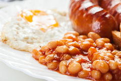Full English breakfast with bacon, sausage, fried egg and baked beans Royalty Free Stock Images