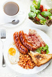 Full English breakfast with bacon, sausage, fried egg and baked beans Stock Image