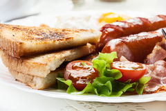 Full English breakfast with bacon, sausage, fried egg and baked beans Stock Photo