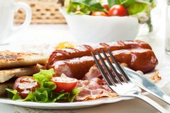 Full English breakfast with bacon, sausage, fried egg and baked Royalty Free Stock Image