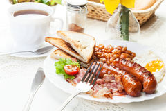 Full English breakfast with bacon, sausage, fried egg and baked Royalty Free Stock Photo