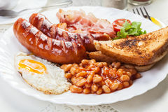 Full English breakfast with bacon, sausage, fried egg and baked beans Stock Photos