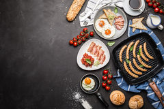Full english breakfast on black chalkboard background. Layout with free text copy space captured from above top view, flat lay. Coffee, fried eggs, baked beans royalty free stock photo