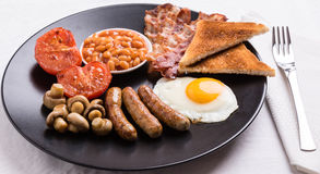 Full english breakfast on black plate Stock Photo