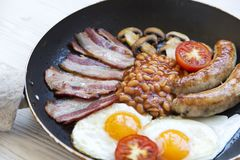 Full English breakfast in cooking pan with fried eggs, bacon, sausages, beans and toasts. Closeup Royalty Free Stock Images