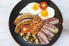 Full English Breakfast in cooking pan with sausages, fried eggs, beans and bacon on a white wooden background. Top view. From abov. E. Flatlay Royalty Free Stock Images