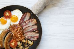 Full English Breakfast in cooking pan with sausages, fried eggs, beans and bacon on a white wooden background, top view. Copy spac. E. From above. Flatlay Royalty Free Stock Photos
