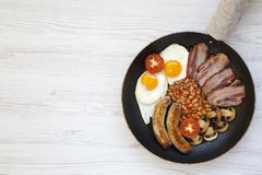 Full English Breakfast in cooking pan with sausages, fried eggs, beans and bacon on a white wooden background. Top view. Copy spac. E. Flat lay. From above Stock Photography