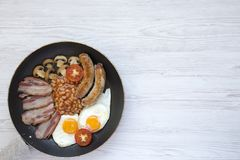 Full English Breakfast in cooking pan with sausages, fried eggs, beans and bacon on a white wooden background, top view. Copy spac. E. From above. Flatlay Stock Photo