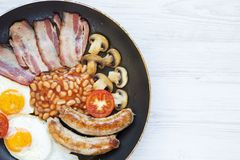 Full English Breakfast in cooking pan with sausages, fried eggs, beans and bacon on a white wooden background, top view. Copy spac. E. From above. Flatlay Stock Image