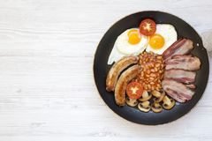 Full English Breakfast in cooking pan with sausages, mushrooms, fried eggs, beans, tomato and bacon on a white wooden background. Copy space. Top view. Flat Royalty Free Stock Images