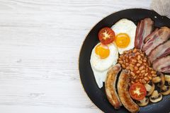 Full English Breakfast in cooking pan with sausages, mushrooms, fried eggs, beans, tomato and bacon on a white wooden background w. Ith copy space. Top view Royalty Free Stock Photography