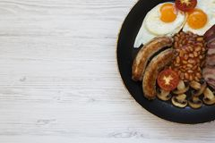 Full English Breakfast in cooking pan with sausages, mushrooms, fried eggs, beans, tomato and bacon on a white wooden background w. Ith copy space. Top view Stock Images