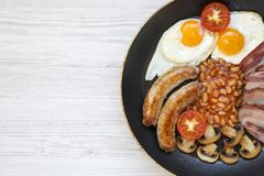 Full English Breakfast in cooking pan with sausages, mushrooms, fried eggs, beans, tomato and bacon on a white wooden background w. Ith copy space. Top view Royalty Free Stock Photos
