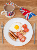 Full english breakfast with cup of tea and british flag. English breakfast on a wooden table with  cup of tea  and british flag in portrait Stock Photo