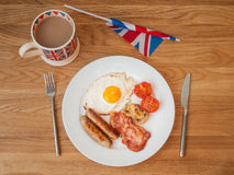 Full english breakfast with cup of tea and british flag. English breakfast on a wooden table with cup of tea  and british flag in landscape Stock Images