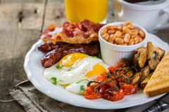 Full english breakfast - eggs, bacon, beans, toast, coffee and juice. Rustic wood background Royalty Free Stock Photo