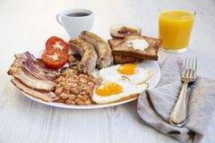 Full english breakfast with fried eggs, bacon, sausages, beans and toasts on white wooden background. Closeup. Side view Stock Photo