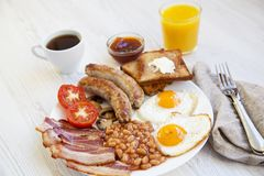 Full english breakfast with fried eggs, bacon, sausages, beans and toasts on white wooden background. Closeup. Side view Royalty Free Stock Photography
