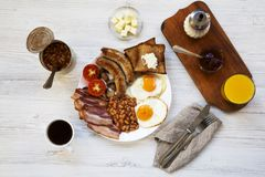 Full english breakfast with fried eggs, bacon, sausages, beans and toasts on white wooden background, top view. Flat lay. From above Royalty Free Stock Photo