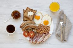 Full english breakfast with fried eggs, bacon, sausages, beans and toasts on white wooden background. Top view. Flat lay. From above Royalty Free Stock Images