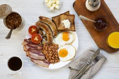 Full English breakfast with fried eggs, bacon, sausages, beans and toasts on white wooden background, top view. Flat lay. From above, overhead Royalty Free Stock Photos