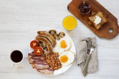 Full English breakfast with fried eggs, beans, bacon, sausages and toasts on a white wooden background, top view. Flat lay. From above, overhead Royalty Free Stock Photos