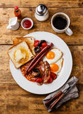 Full English Breakfast. With fried eggs, sausages, bacon, beans, toasts, tomatoes and mushrooms on wooden background Royalty Free Stock Images