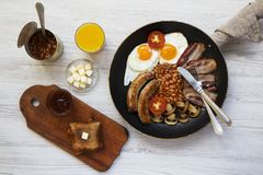 Full english breakfast in a frying pan with fried eggs, bacon, sausages, beans and toasts on white wooden background, top view., s. Full english breakfast in a Stock Image