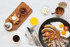 Full English breakfast in a pan with fried eggs, bacon, beans, sausages  and toasts on white wooden background, top view. From abo. Ve, flat lay Royalty Free Stock Images