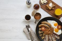 Full English breakfast in a pan with fried eggs, bacon, beans, sausages  and toasts on white wooden background, top view. Copy spa. Ce. Flat lay. From above Stock Photo