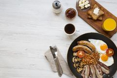 Full English breakfast in a pan with fried eggs, bacon, beans, sausages  and toasts on white wooden background, top view. Copy spa. Ce. Flat lay. From above Stock Photography