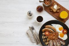 Full English breakfast in a pan with fried eggs, bacon, beans, sausages  and toasts on white wooden background, top view. Flat lay. From above. Copy space Royalty Free Stock Images