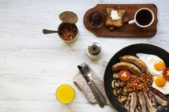 Full English breakfast in a pan with fried eggs, bacon, beans, sausages  and toasts on white wooden background, top view. Copy space. Flat lay. From above Stock Images