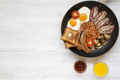 Full English breakfast in a pan with fried eggs, bacon, sausages, beans, toasts and orange juice on white wooden background with c. Opy space, top view. Flat lay Stock Image