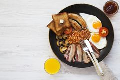 Full English breakfast in a pan with fried eggs, bacon, sausages, beans, toasts and orange juice on white wooden background, top v. Iew. Flat lay. From above Royalty Free Stock Image