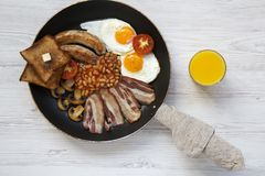 Full English breakfast in a pan with fried eggs, bacon, sausages, beans, toasts and orange juice on white wooden background, top v. Iew. Flat lay. From above Royalty Free Stock Photos
