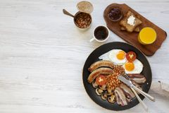 Full English breakfast in a pan with fried eggs, bacon, sausages, beans and toasts on white wooden background, top view. Copy spac. E. Flat lay. From above Royalty Free Stock Images